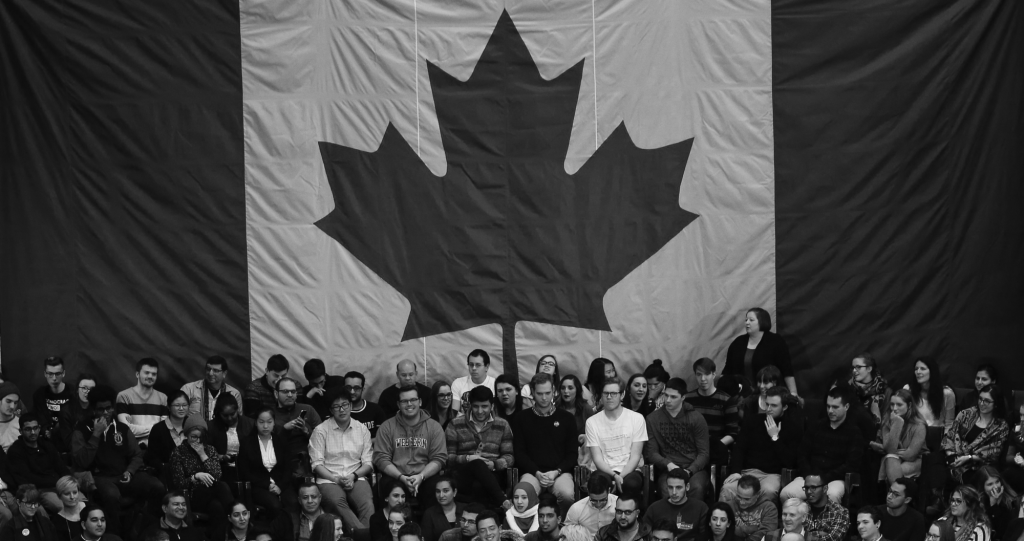 A large group of people sitting in front of a Canadian flag