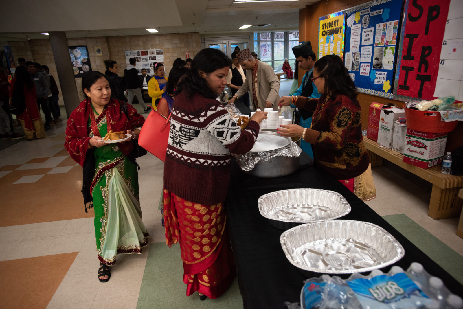 Women in colourful Bhutanese clothing gather around atable to serve food at a Diwali festival in Halifax.