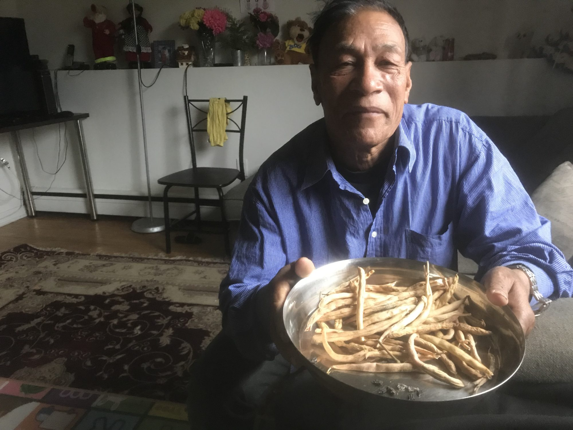 Chandra Bahadur Pradhan holds a bowl with crop from the community garden