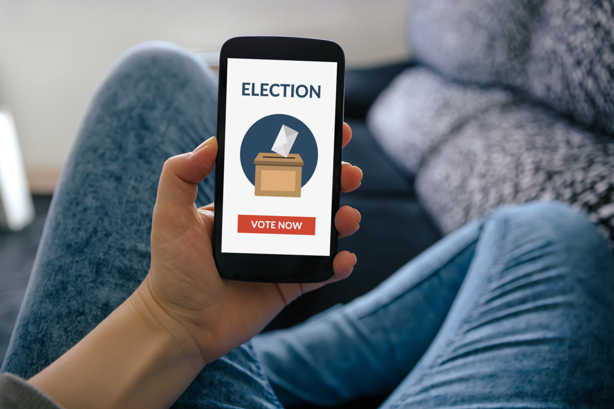 Girl holding smart phone with online voting concept on screen.