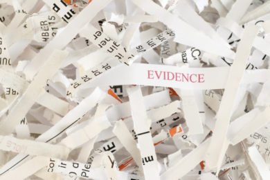 Shredded paper with the word EVIDENCE written on one of the pieces of paper demonstrating evidence destruction and possible obstruction of justice