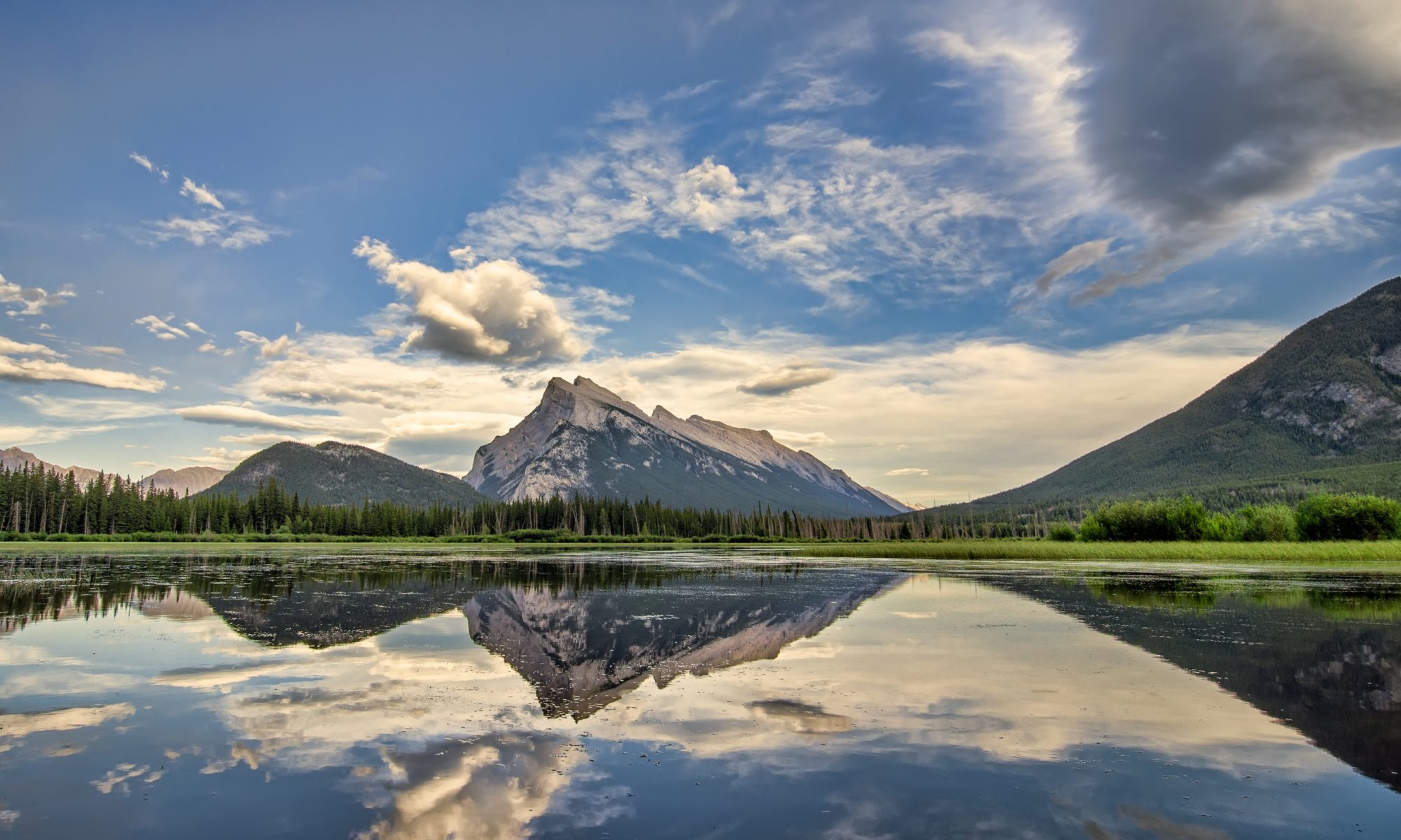 Mountain range and cloudy sky reflecting on a calm body of water.