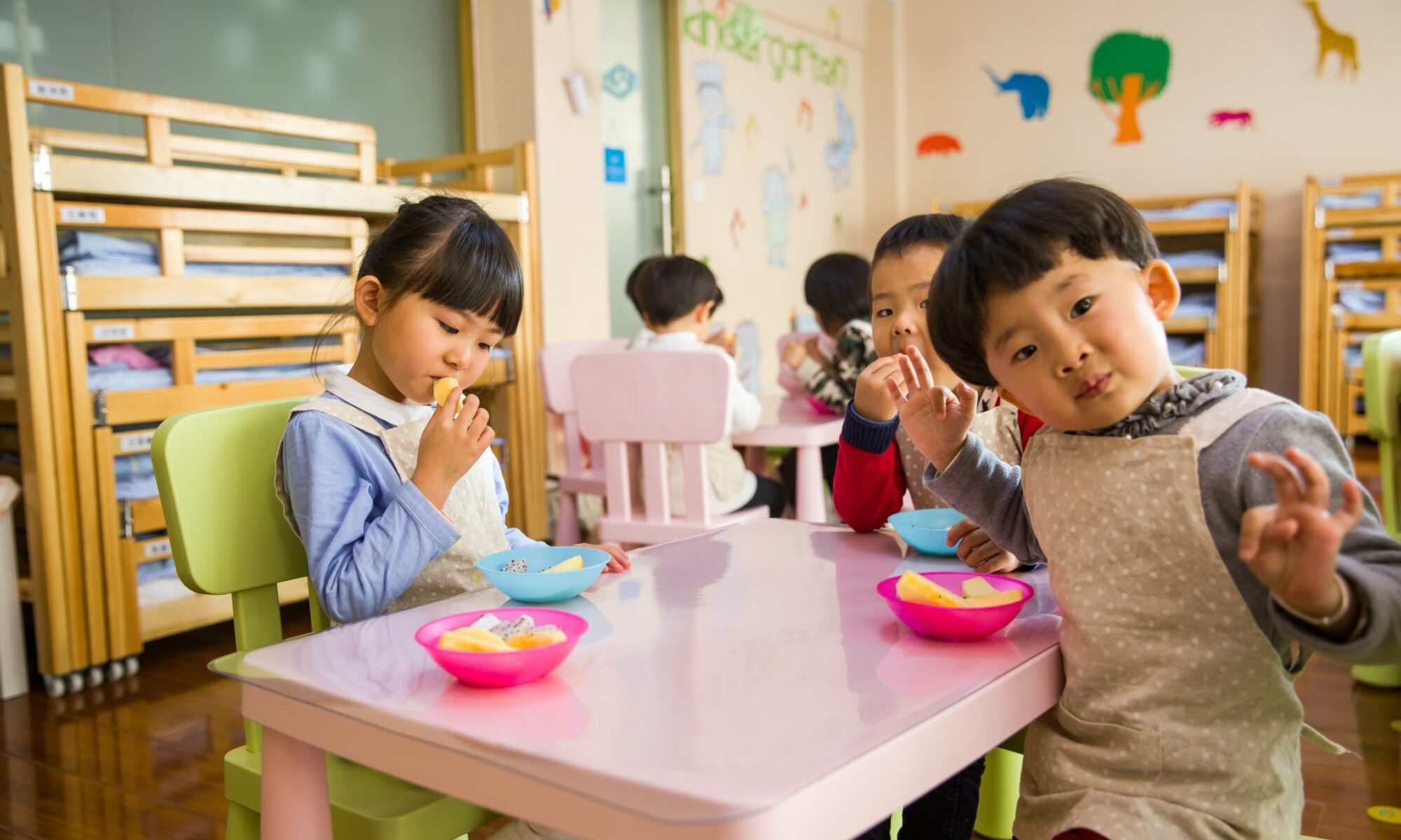 children sitting together at a table in a childcare facility
