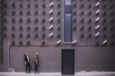 Two people looking up standing under a wall of CCTV cameras