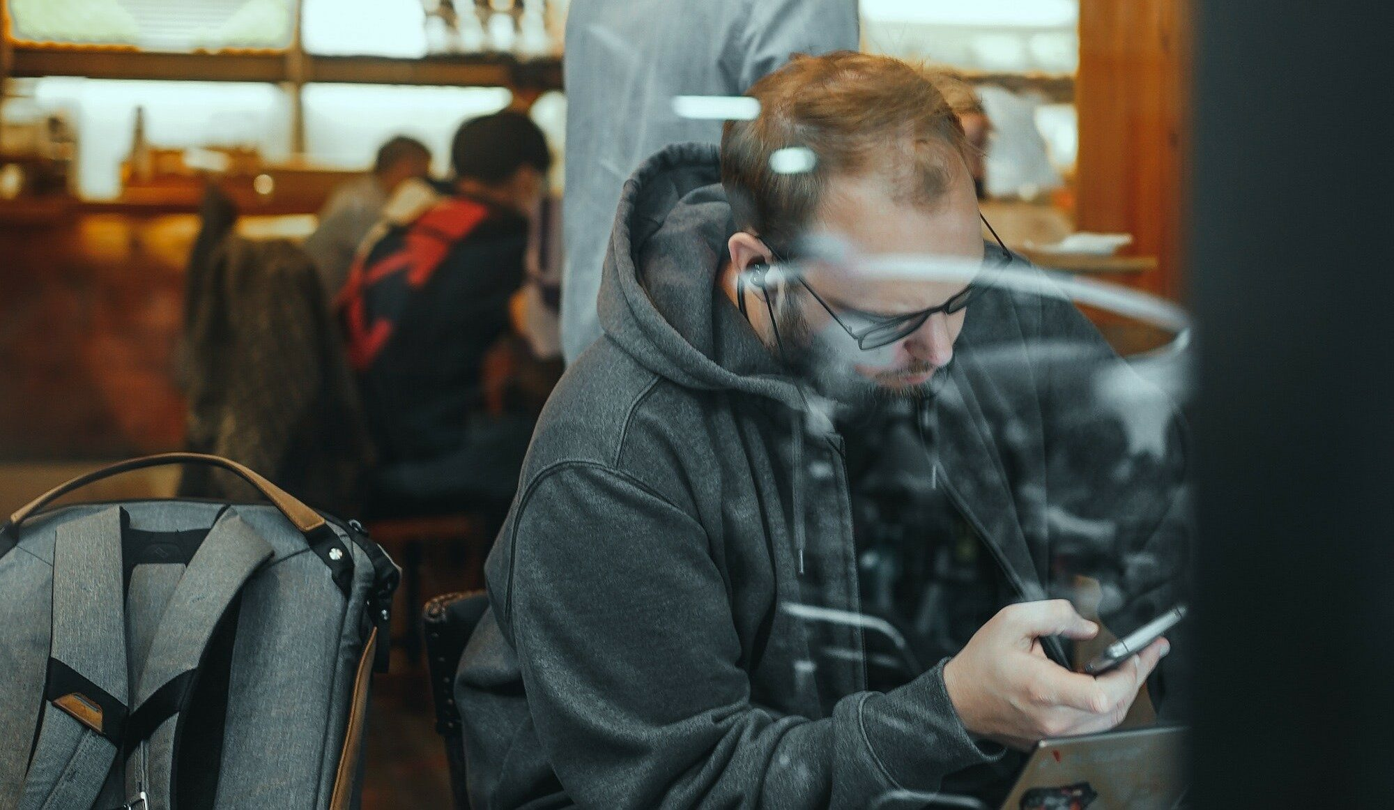 A man in a grey sweatshirt, wearing black ear buds, scrolls through his phone with his laptop open in front of him. On the chair to his left sits a grey and brown backpack. Behind him, the movement of what looks to be a busy cafe