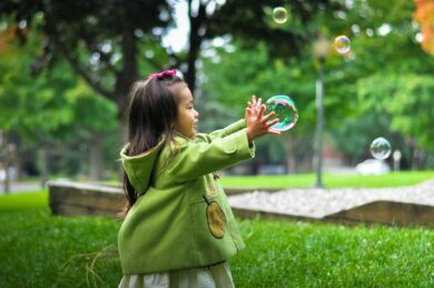 A young girl catching a bubble outside